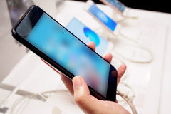 Mulher que escolhe o smartphone móvel novo na loja imagem de stock