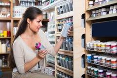 A mulher que escolhe a pintura no aerossol pode na loja fotos de stock