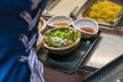 Mulher que escolhe a salada, vegetal no bufete imagens de stock royalty free