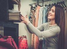 Mulher que escolhe sapatas em uma loja Fotografia de Stock