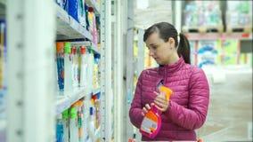 Mulher que escolhe um líquido de limpeza de janela no supermercado video estoque