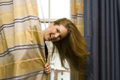 Mulher que esconde atrás das cortinas Fotos de Stock
