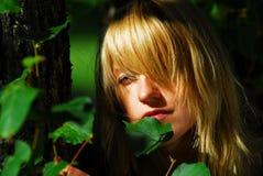 Mulher que esconde nas folhas Imagens de Stock Royalty Free