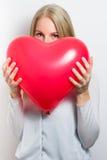 Mulher que esconde sua cara atrás de um coração vermelho Fotos de Stock Royalty Free