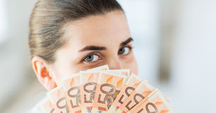 Mulher que esconde sua cara atrás do euro- fã do dinheiro Imagens de Stock Royalty Free
