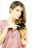 Mulher que escova o cabelo bonito longo de seda que olha a câmera imagem de stock