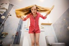 Mulher que escova seu cabelo longo fotografia de stock