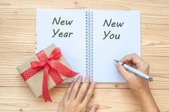 Mulher que escreve a 2019 anos novos novo o palavra com caderno e decoração do Natal na tabela de madeira, na vista superior e no fotos de stock
