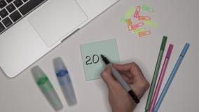 Mulher que escreve 2020 no bloco de notas Portátil e artigos de papelaria na tabela video estoque