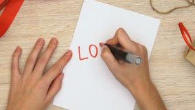 Mulher que escreve a palavra do amor no papel, o relacionamento romântico entre o homem e a mulher video estoque