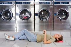 Mulher que escuta a música ao encontrar-se na lavanderia foto de stock royalty free