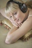 Mulher que escuta a música através dos fones de ouvido ao descansar no coxim foto de stock
