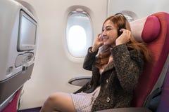 A mulher que escuta a m?sica com os fones de ouvido no avi?o cronometra em voo foto de stock