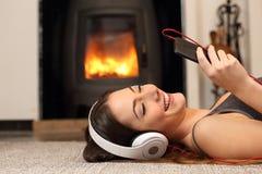 Mulher que escuta a música de um smartphone em casa Fotografia de Stock Royalty Free
