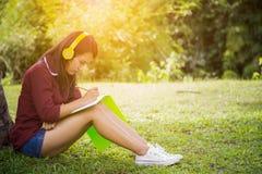 Mulher que escuta a música e que escreve no caderno sob a árvore Fotos de Stock