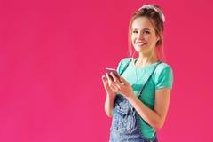 A mulher que escuta a música nos fones de ouvido forma o móbil Imagens de Stock