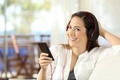 Mulher que escuta a música que olha a câmera em casa Imagem de Stock