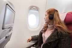 A mulher que escuta a m?sica com os fones de ouvido no avi?o cronometra em voo imagens de stock