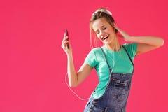 A mulher que escuta a música nos fones de ouvido forma o móbil Foto de Stock