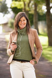 Mulher que escuta o MP3 enquanto andando Fotos de Stock Royalty Free