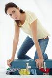 Mulher que esforça-se para fechar a mala de viagem Fotos de Stock