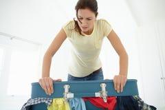 Mulher que esforça-se para fechar a mala de viagem Imagens de Stock