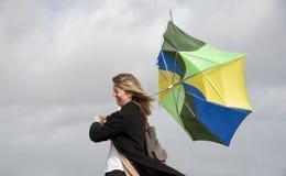 Mulher que esforça-se para guardar seu guarda-chuva em um dia ventoso Fotografia de Stock