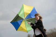 Mulher que esforça-se para guardar seu guarda-chuva em um dia ventoso imagens de stock royalty free