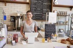 Mulher que espera atrás do contador em uma cafetaria, fim acima imagens de stock royalty free