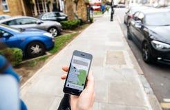 Mulher que espera o carro do uber na rua que guarda o smartphone fotos de stock