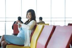Mulher que espera seu voo Fotos de Stock Royalty Free