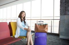 Mulher que espera seu voo Imagens de Stock