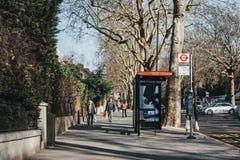 Mulher que espera um ônibus em Holland Park, em Kensington e em Chelsea, Londres, Reino Unido fotos de stock