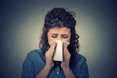 Mulher que espirra em um tecido que funde seu nariz ralo Imagem de Stock