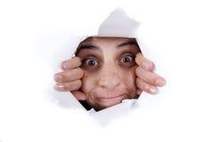 Mulher que espreita atrás do furo da parede Fotografia de Stock Royalty Free