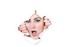 Mulher que espreita através do furo no papel Imagens de Stock Royalty Free