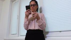 Mulher que espreme a bola do esforço e que usa o smartphone video estoque