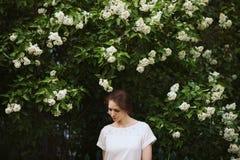 Mulher que está ao lado de um arbusto do lilás branco fotos de stock royalty free