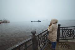 Mulher que está apenas na costa de mar e que olha no navio Tempo de inverno Esposa do ` s do marinheiro Imagem de Stock