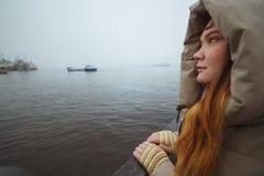 Mulher que está apenas na costa de mar e que olha no navio Tempo de inverno Esposa do ` s do marinheiro Fotografia de Stock