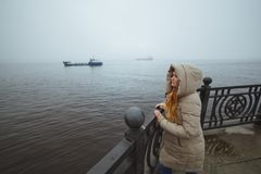 Mulher que está apenas na costa de mar e que olha no navio Tempo de inverno Esposa do ` s do marinheiro Imagens de Stock Royalty Free