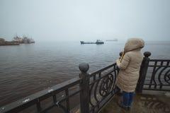 Mulher que está apenas na costa de mar e que olha no navio Tempo de inverno Esposa do ` s do marinheiro Foto de Stock