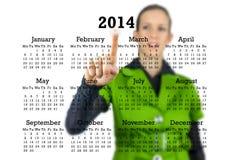 Mulher que está atrás de um calendário 2014 Fotos de Stock Royalty Free