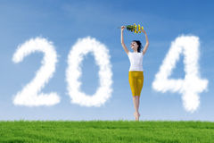 Mulher que está com as 2014 nuvens do ano novo Fotos de Stock