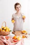 Mulher que está dentro e que guarda citrinos nas mãos Foto de Stock