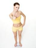 Mulher que está em escalas e em mostras o thumbs-up Fotos de Stock Royalty Free