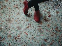 Mulher que está em um tapete oriental colorido do teste padrão com as sapatas do vermelho da forma Fotografia de Stock