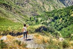 Mulher que está na borda da rocha e que olha o Mountain View impressionante Fotos de Stock Royalty Free
