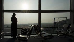 Mulher que está na janela do aeroporto Imagens de Stock Royalty Free