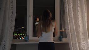 Mulher que está na janela que olha a noite exterior e a iluminação 4k video estoque